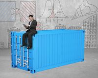 Businessman sitting on 3d blue cargo container Royalty Free Stock Image