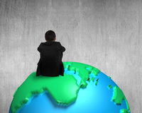 Businessman sitting on 3d map globe watching blank concrete wall. Background Stock Image