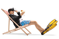 Businessman sitting in a deck chair and using a VR headset Stock Photos