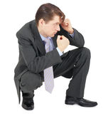 Businessman sitting in defensive pose Stock Photo