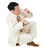 Businessman sitting in defensive posture Stock Images