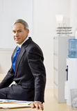 Businessman sitting on desk Stock Photo