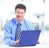 Businessman sitting by desk Stock Photography