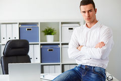 Businessman sitting on desk with arms crossed in office Royalty Free Stock Photo