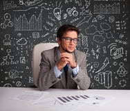 Businessman sitting at desk with business scheme and icons. Young businessman sitting at desk with business scheme and icons Stock Photos