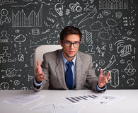 Businessman sitting at desk with business scheme and icons Royalty Free Stock Photo