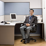 Businessman sitting at desk in cubicle. Businessman sitting at his cubicle desk Royalty Free Stock Photo