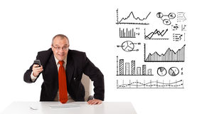 Businessman sitting at desk with diagrams and graphs Stock Image