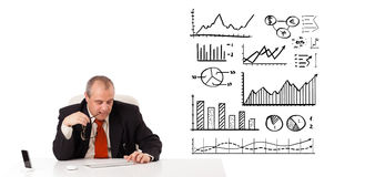Businessman sitting at desk with diagrams and graphs Royalty Free Stock Image