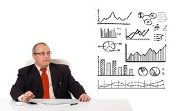 Businessman sitting at desk with diagrams and graphs Royalty Free Stock Photography