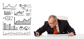 Businessman sitting at desk with diagrams and graphs. On white Royalty Free Stock Photos