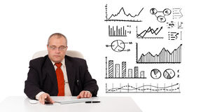 Businessman sitting at desk with diagrams and holding a mobileph Royalty Free Stock Photos