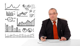 Businessman sitting at desk with diagrams and holding a mobileph Stock Image