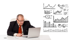 Businessman sitting at desk with diagrams and laptop Royalty Free Stock Photography