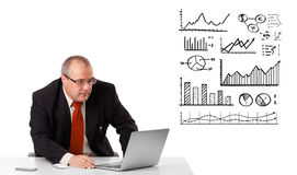Businessman sitting at desk with diagrams and laptop Stock Image