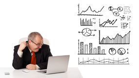 Businessman sitting at desk with diagrams and laptop Royalty Free Stock Images