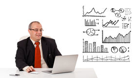 Businessman sitting at desk with diagrams and laptop Stock Photos