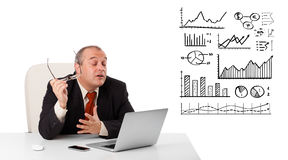 Businessman sitting at desk with diagrams and laptop Stock Photo