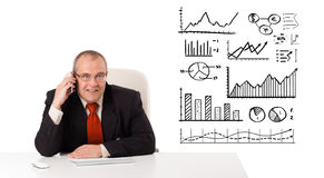 Businessman sitting at desk with diagrams and making a phone cal Stock Image