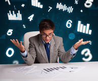 Businessman sitting at desk with diagrams and statistics Stock Images