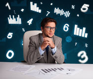 Businessman sitting at desk with diagrams and statistics Royalty Free Stock Photography