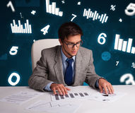 Businessman sitting at desk with diagrams and statistics Stock Photography
