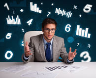 Businessman sitting at desk with diagrams and statistics. Young businessman sitting at desk with diagrams and statistics Stock Photo