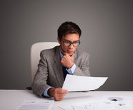 Businessman sitting at desk and doing paperwork Stock Photography