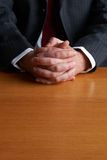 Businessman Sitting At Desk With Folded Hands. Businessman Sits At Desk With Folded Hands Royalty Free Stock Photo
