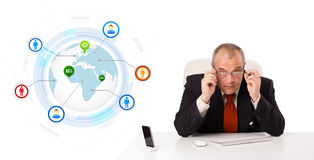 Businessman sitting at desk with a globe and social icons Stock Photo