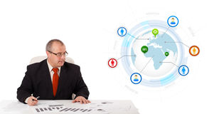 Businessman sitting at desk with a globe and social icons Royalty Free Stock Photography