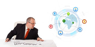 Businessman sitting at desk with a globe and social icons Royalty Free Stock Image
