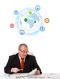 Businessman sitting at desk with a globe and social icons Royalty Free Stock Photo