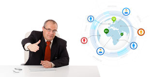 Businessman sitting at desk with a globe and social icons Stock Photos
