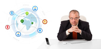 Businessman sitting at desk with a globe and social icons Stock Photography
