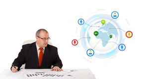 Businessman sitting at desk with a globe and social icons Stock Images