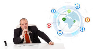 Businessman sitting at desk with a globe and social icons Royalty Free Stock Images