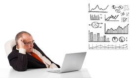 Businessman sitting at desk with graphs and laptop Stock Photography
