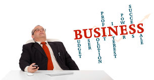 Businessman sitting at desk and holding a mobilephone with busin Royalty Free Stock Photos