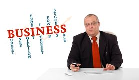 Businessman sitting at desk and holding a mobilephone with busin. Ess word cloud, isolated on white Royalty Free Stock Photography