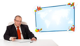 Businessman sitting at desk and holding a mobilephone with copy Stock Photography