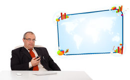 Businessman sitting at desk and holding a mobilephone with copy Royalty Free Stock Images
