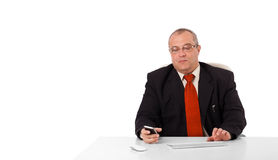 Businessman sitting at desk and holding a mobilephone with copys. Pace, isolated on white Stock Photo