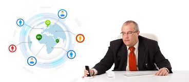 Businessman sitting at desk and holding a mobilephone with globe Royalty Free Stock Photo
