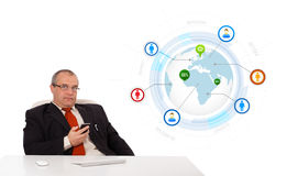 Businessman sitting at desk and holding a mobilephone with globe Stock Photo