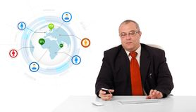 Businessman sitting at desk and holding a mobilephone with globe Stock Photography