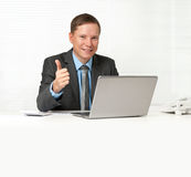 Businessman sitting at desk with laptop Royalty Free Stock Photos