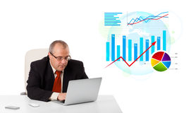 Businessman sitting at desk with laptop and statistics Stock Image