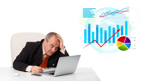 Businessman sitting at desk with laptop and statistics Stock Photo