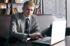Businessman sitting at desk with laptop. Young businessman sitting at desk with laptop. looking at the camera and smiling. the hand is on the laptop Stock Photos